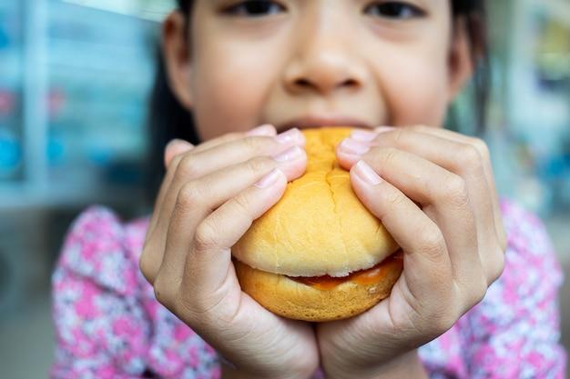 Menina asiática que come um hamburger. Foto Premium