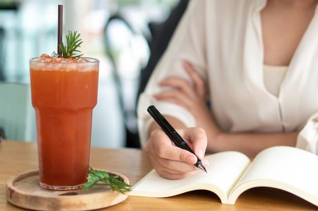 Menina asiática que guarda uma escrita preta da pena em um livro vazio. diário escrevendo histórias Foto Premium