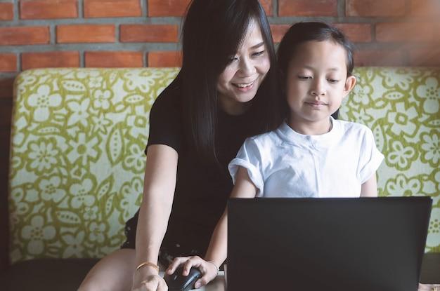 Menina asiática que joga no portátil com sua mãe em casa. Foto Premium