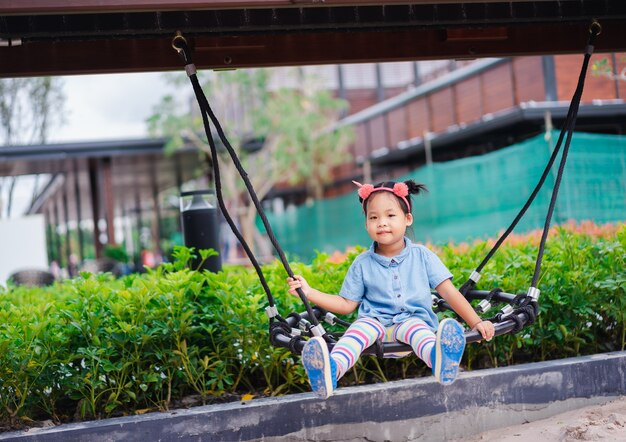 Menina asiática que senta-se em um balanço no campo de jogos das crianças Foto Premium