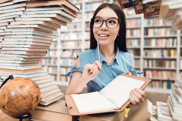 Menina asiática que senta-se na tabela cercada por livros na biblioteca. Foto Premium