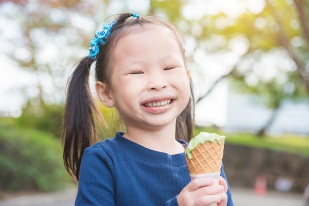 Menina asiática que sorri com a boca suja ao comer o gelado no parque Foto Premium