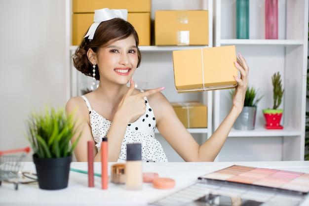 Menina asiática que trabalha no escritório home e que classifica a caixa do cargo para o serviço de entrega ao cliente Foto gratuita