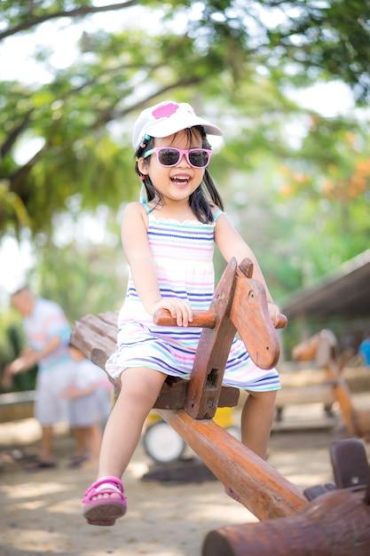 Menina asiática se divertindo na gangorra no playground Foto Premium