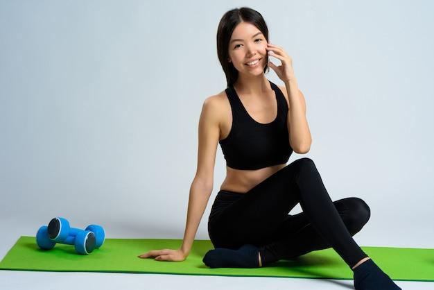 Menina asiática sentado e falando ao telefone. Foto Premium