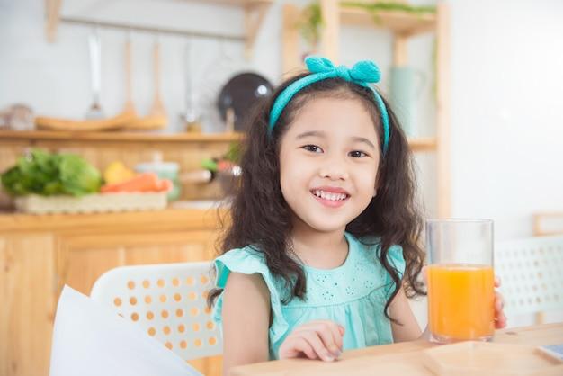 Menina asiática sorrindo enquanto bebe suco de laranja na mesa de café da manhã Foto Premium
