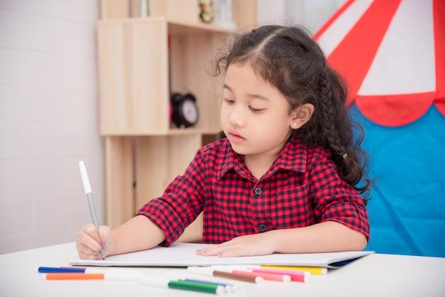 Menina asiática tirando foto por marcador de cor na mesa em casa Foto Premium