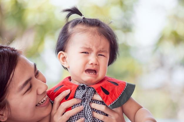 Menina asiática triste chorando e mãe consolá-la com amor Foto Premium