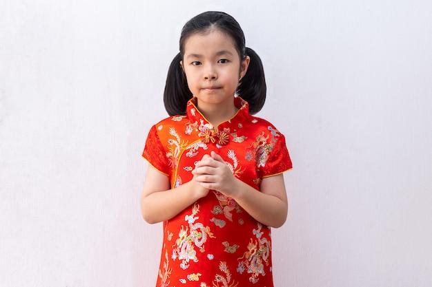 Menina asiática usar cheongsam com gesto de parabéns, reunir as mãos em saudação. no ano novo chinês Foto Premium