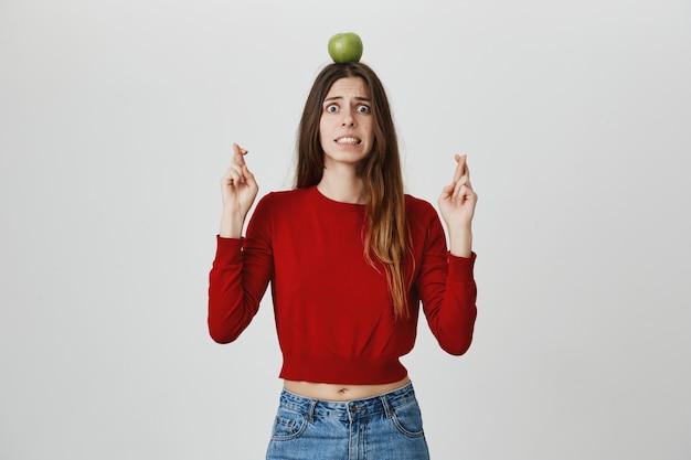 Menina assustada e preocupada com alvo de maçã na cabeça rezando, cruzar os dedos com medo do perigo Foto gratuita