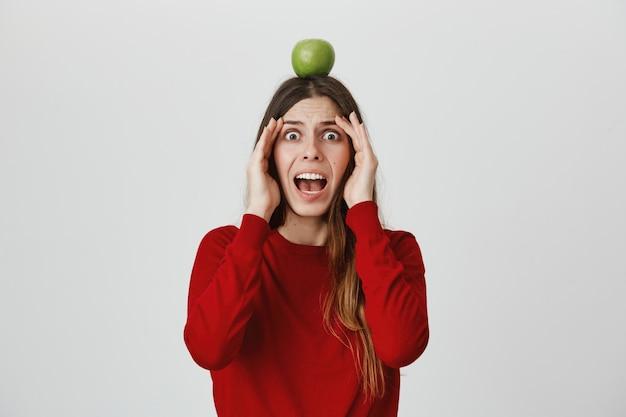 Menina assustada gritar em pânico como ver flecha voadora, segurando o alvo de maçã na cabeça Foto gratuita