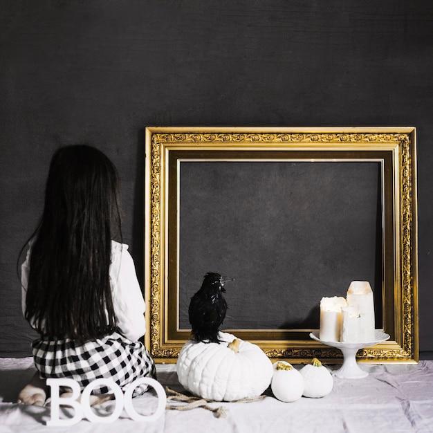 Menina assustadora e corvo olhando o quadro Foto gratuita