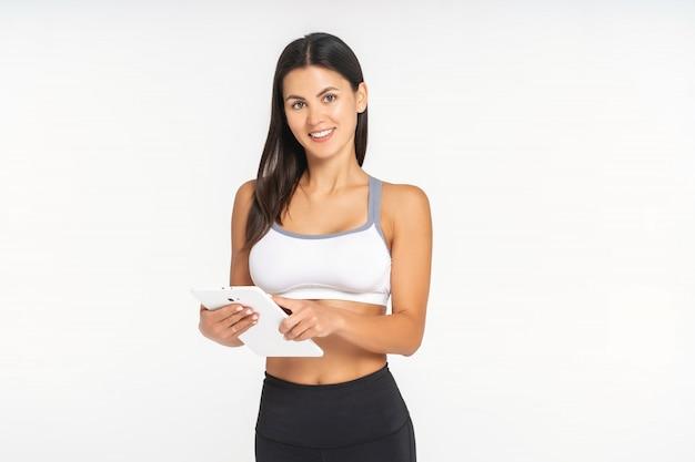 Menina atleta está assistindo um aplicativo de esportes em um tablet Foto Premium
