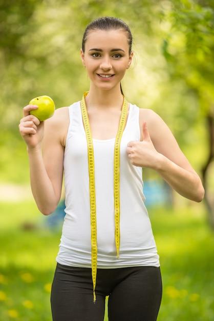 Menina atlética nova que come a maçã verde após o exercício. Foto Premium