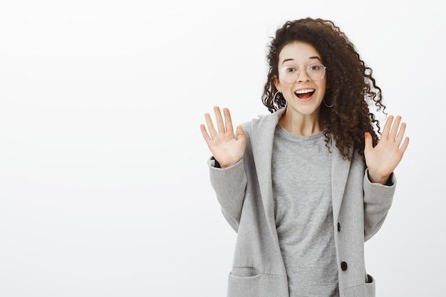 Menina atordoada com notícias incríveis de bestie. retrato de uma mulher europeia feliz satisfeita com cabelo encaracolado de óculos e casaco cinza, levantando as mãos e sorrindo de felicidade Foto gratuita