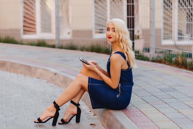 Menina atrativa loura emotiva nos óculos de sol com o telefone no sol do verão urbano Foto Premium