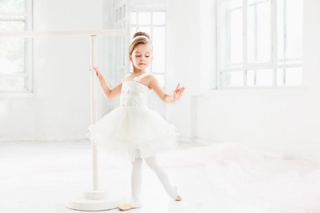 Menina bailarina em um tutu. criança adorável que dança o balé clássico em um estúdio branco. Foto gratuita