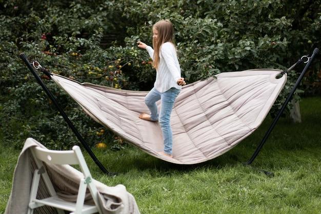 Menina balançando em pé em uma rede Foto gratuita