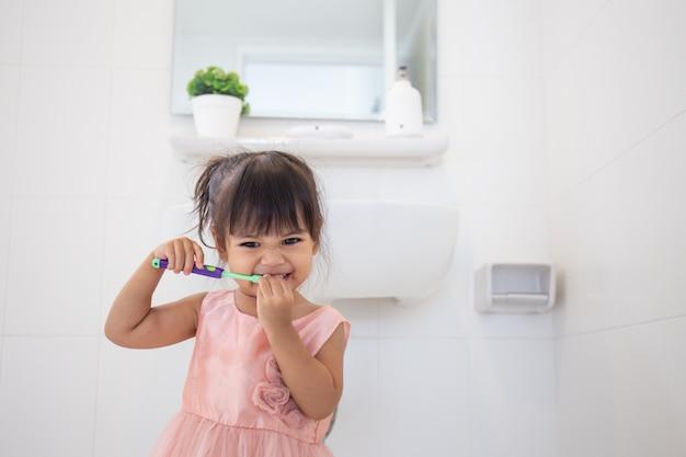 Menina bebê fofo limpando os dentes com escova de dentes no banheiro Foto Premium