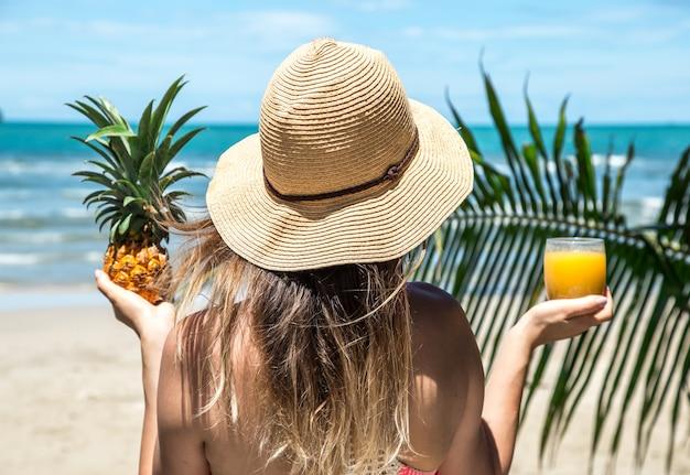 Menina bebe suco na praia Foto Premium