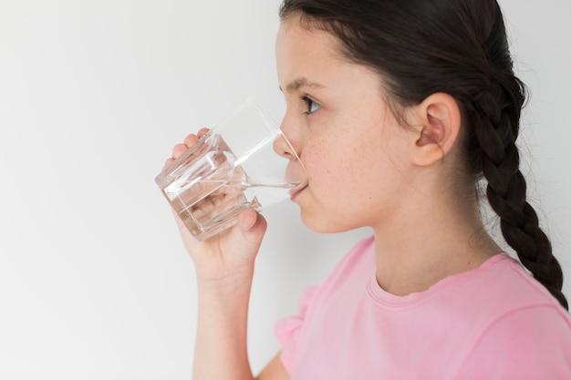 Menina bebendo água dentro de casa Foto gratuita