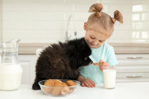 Menina bebendo leite e brincando com cachorro em casa Foto gratuita