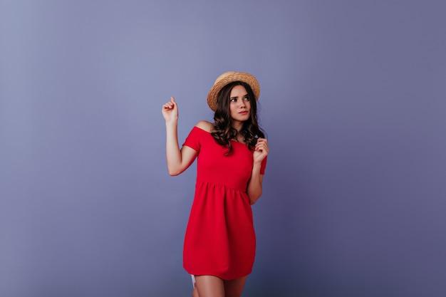 Menina bem vestida pensativa, posando na parede roxa. mulher atraente de cabelos escuros com vestido vermelho e chapéu de palha, desfrutando da sessão de fotos. Foto gratuita