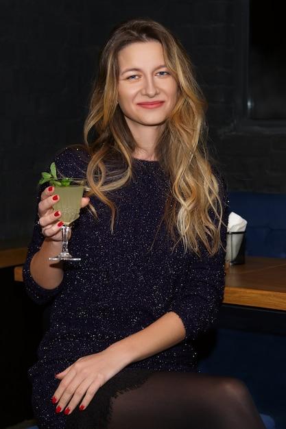 Menina bonita, a beber cocktails no bar Foto Premium
