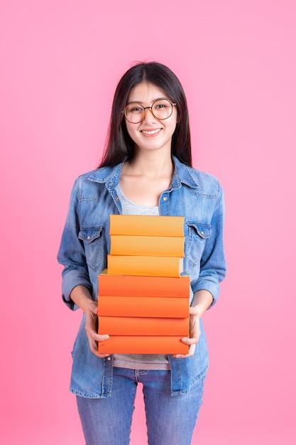 Menina bonita adolescente de retrato segurando a pilha de livros e smiley em rosa, conceito de teenge de educação Foto gratuita
