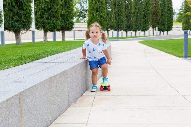 Menina bonita aprendendo a andar de skate Foto Premium