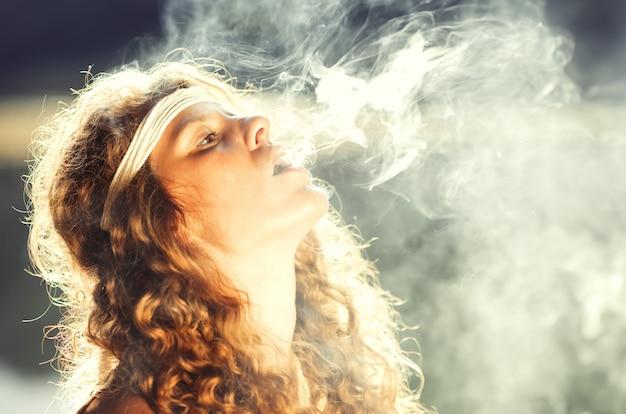 Menina bonita bonita hippie soprando fumaça Foto Premium
