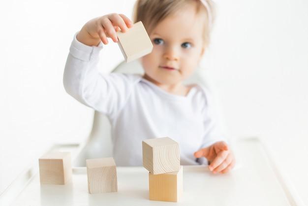 Menina bonita, brincando com cubos de madeira. torre de construção de criança pequena. bloco de construção para crianças. método educacional montessori. foco seletivo Foto Premium