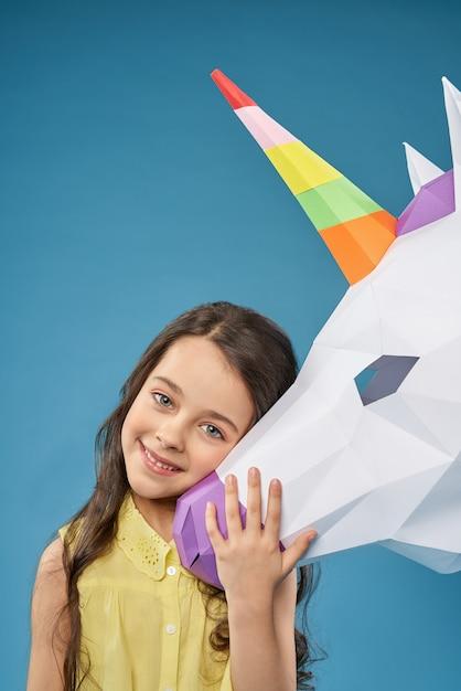 Menina bonita brincando com unicórnio de papel e rindo Foto gratuita