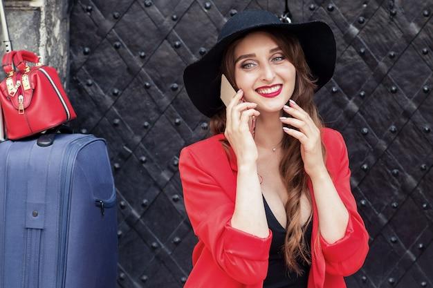 Menina bonita caucasiana com uma mala está falando no telefone inteligente perto da porta antiga. Foto Premium