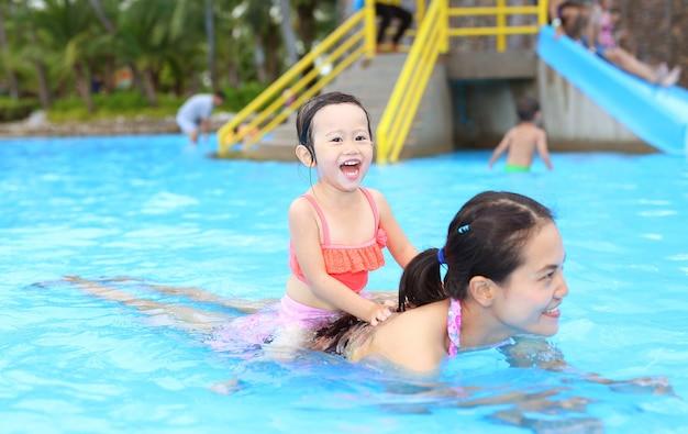 Menina bonita com a mãe dela brincando na piscina ao ar livre Foto Premium