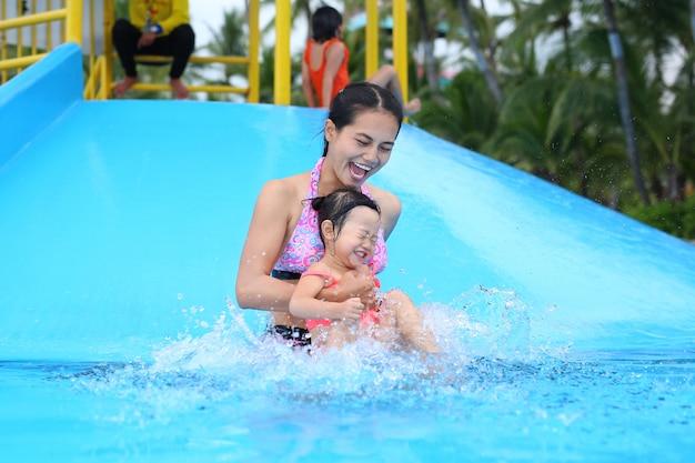Menina bonita com a mãe dela deslizando na piscina ao ar livre Foto Premium