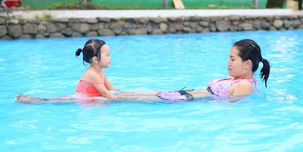 Menina bonita com a mãe na piscina ao ar livre Foto Premium