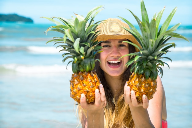Menina bonita com abacaxi em uma praia exótica, um clima feliz e um sorriso lindo Foto Premium