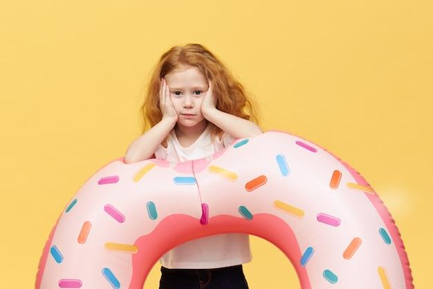 Menina bonita com cabelo comprido e círculo inflável de natação Foto gratuita