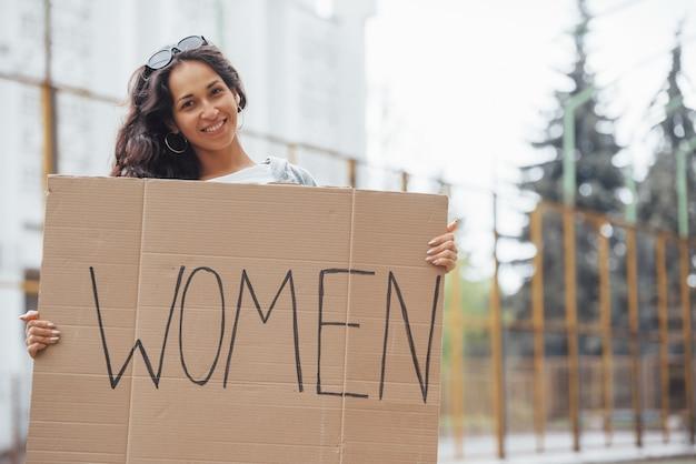 Menina bonita com cabelo encaracolado com um pôster feminista feito à mão nas mãos Foto Premium