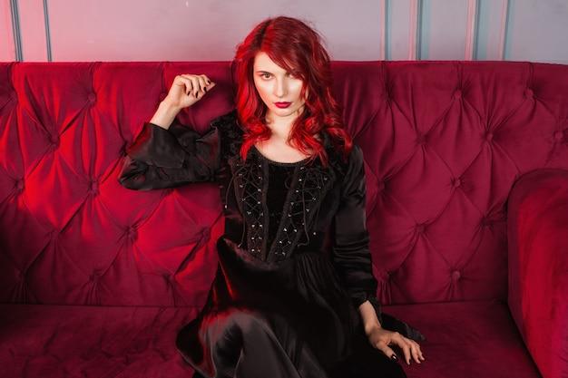 Menina bonita com cabelo vermelho e maquiagem natural e pele pálida. uma mulher em um vestido preto retrô, sentado num sofá vermelho. modelo posando. a aparência incomum. mulher insidiosa bruxa malvada. Foto Premium