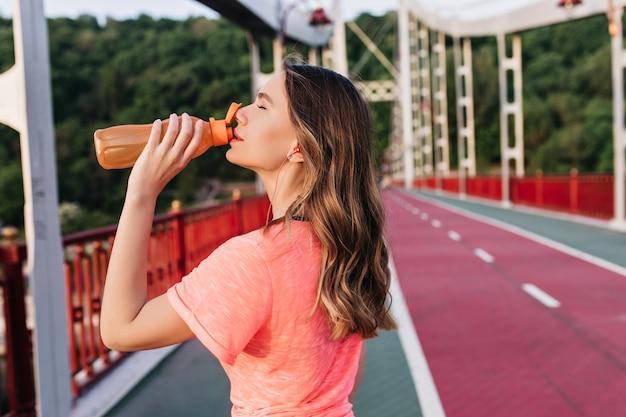 Menina bonita com cabelos ondulados bebendo água após maraphon. senhora caucasiana refinada, posando em pista de concreto durante o treinamento. Foto gratuita