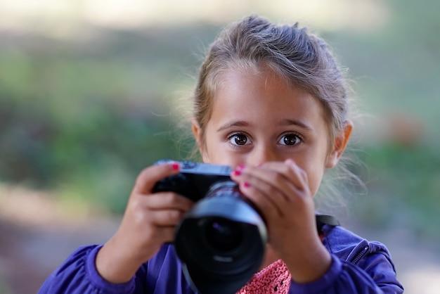 Menina bonita com câmera fotográfica tira fotos Foto Premium