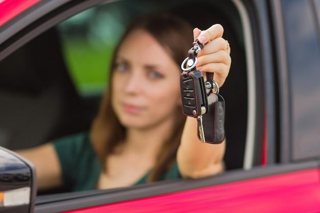 Menina bonita com chaves do carro na mão, conceito de comprar um carro novo Foto Premium