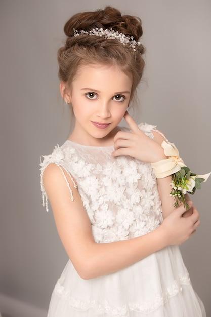 Menina bonita com flores vestidas em vestidos de noiva Foto gratuita