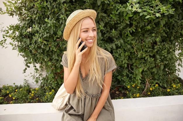 Menina bonita com longos cabelos loiros posando sobre arbustos verdes, usando um vestido romântico e velejador, segurando o telefone na mão e olhando para o lado com alegria Foto gratuita