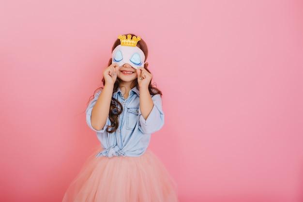 Menina bonita com longos cabelos morenos em saia de tule, segurando uma máscara de dormir com olhos azuis e coroa dourada isolada no fundo rosa. comemorando festa de aniversário, se divertindo no carnaval para crianças Foto gratuita