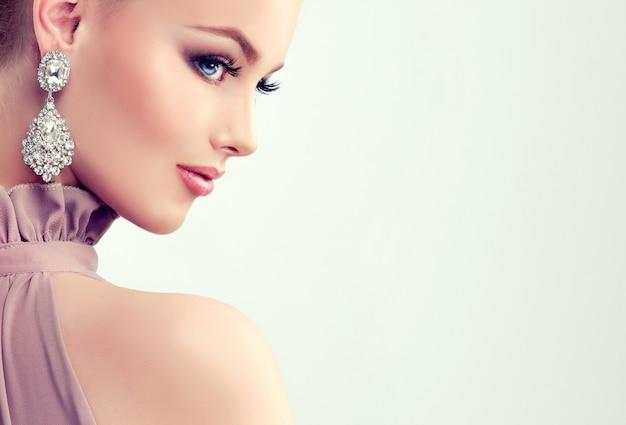 Menina bonita com maquiagem de noite e grandes brincos de jóias Foto Premium