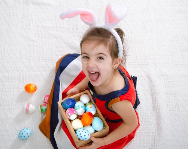 Menina bonita com ovos de páscoa e orelhas de coelho em um lindo vestido brilhante. Foto gratuita