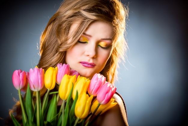 Menina bonita com tulipas flores Foto Premium